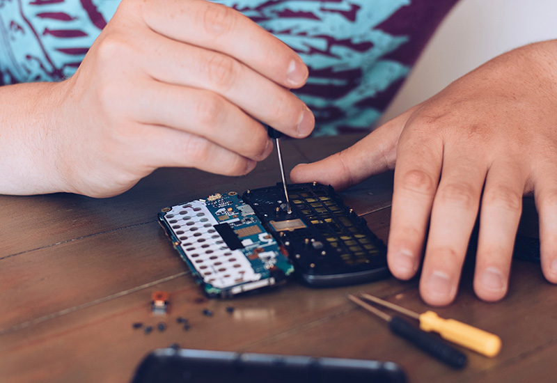Joven está usando un destornillador para reparar un viejo teléfono móvil desmontado