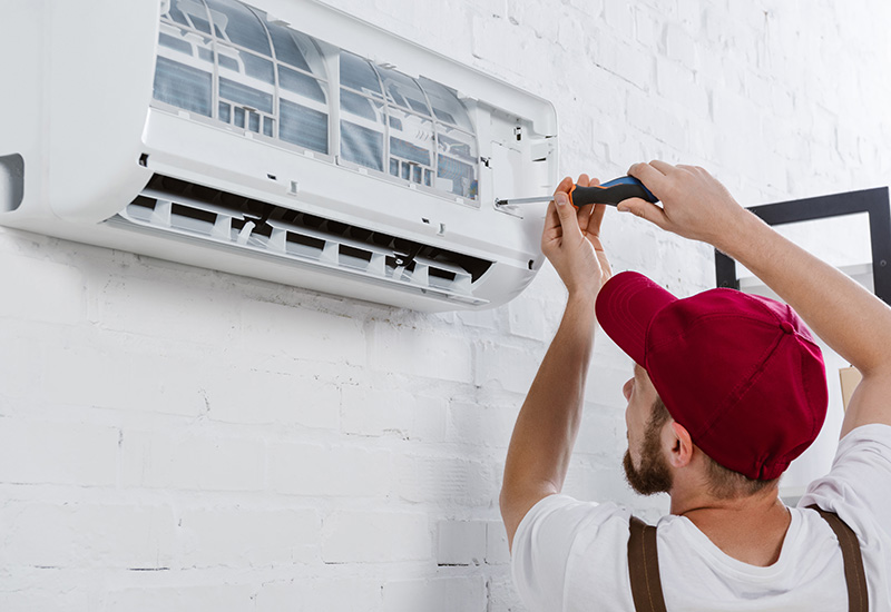 primer plano de reparador profesional cambiador filtro para acondicionador de aire con destornillador